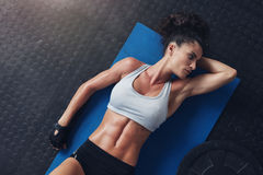 Fitness woman resting after physical training. Top view of fitness woman resting on exercise mat after her physical training session. Young female in sportswear Royalty Free Stock Images