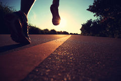 Fitness woman runner legs running on city road Stock Photography