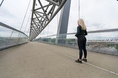 Fitness woman runner rests before running intervall workout on bridge. Fitness woman runner prepare for running intervall workout on bridge in modern looking royalty free stock photography
