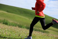 Fitness woman runner running on grassland mountain top Royalty Free Stock Images
