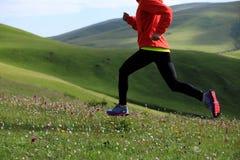 Fitness woman runner running on grassland mountain top Stock Image