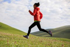 Fitness woman runner running on grassland mountain top Stock Images