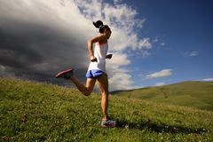 Fitness woman runner running on mountain grassland under dark clouds Royalty Free Stock Images