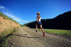 Fitness woman runner running on mountain trail. Young fitness woman runner running on mountain trail Royalty Free Stock Photos
