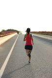 Fitness woman runner running on road Royalty Free Stock Image