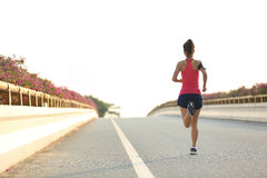 Fitness woman runner running on road. Young fitness woman runner running on road Royalty Free Stock Photography