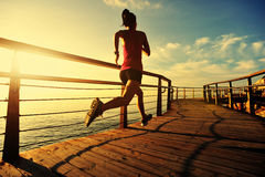 Fitness woman runner running at seaside boardwalk Royalty Free Stock Photo