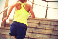 Fitness woman runner running on seaside stone stairs Stock Photography