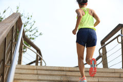 Fitness woman runner running on seaside stone stairs Royalty Free Stock Images