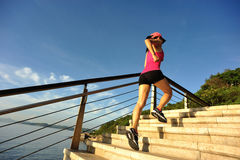 Fitness woman runner running on seaside stone stairs Royalty Free Stock Photos