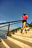 Fitness woman runner running on seaside stone stairs Royalty Free Stock Image