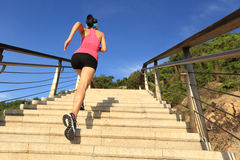 Fitness woman runner running on seaside stone stairs Royalty Free Stock Photo