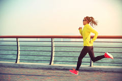 Fitness woman runner running on seaside Stock Photography