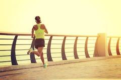 Fitness woman runner running on seaside Royalty Free Stock Photos