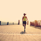 Fitness woman runner running on seaside Stock Image