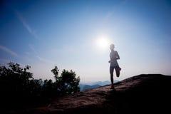Runner running on sunrise mountain top edge Stock Images