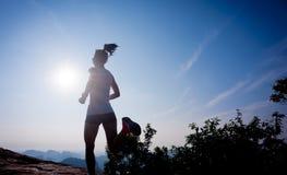 Runner running on sunrise mountain top edge Stock Image