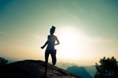 Runner running on sunrise mountain top edge Royalty Free Stock Image