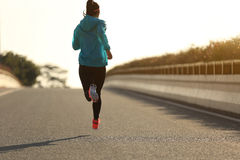 Fitness woman runner running on sunrise road Royalty Free Stock Photography