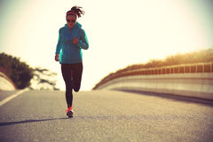 Fitness woman runner running on sunrise road Stock Photo