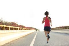 Fitness woman runner running on sunrise road Royalty Free Stock Images