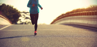Fitness woman runner running on sunrise road Royalty Free Stock Photos