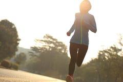 Fitness woman runner running on sunrise road Stock Image