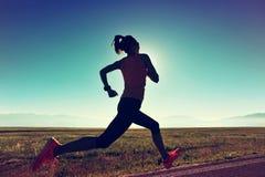 Fitness woman runner running on sunrise seaside trail. Young fitness woman runner running on sunrise seaside trail royalty free stock photography