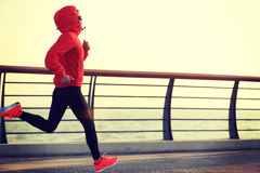 Fitness woman runner running at sunrise seaside Royalty Free Stock Photography