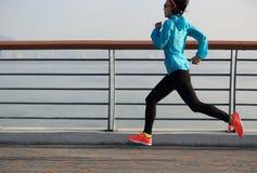 Fitness woman runner running at sunrise seaside Stock Image