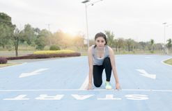 Fitness woman runner in start position at health park. On morning, healthy concept Stock Images