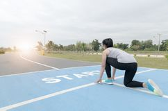 Fitness woman runner in start position at health park. On morning, healthy concept stock image
