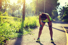 Fitness woman runner take a break at morning tropical forest trail. Young fitness woman runner take a break at morning tropical forest trail stock images
