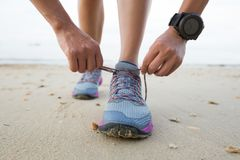 Fitness woman runner tying shoelace on beach. Healthy lifestyle young fitness woman runner tying shoelace on beach Stock Photography