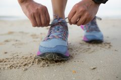 Fitness woman runner tying shoelace on beach. Healthy lifestyle young fitness woman runner tying shoelace on beach Royalty Free Stock Photos