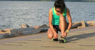 Healthy lifestyle fitness woman runner tying shoelace before running on sunny seaside. Fitness woman runner tying shoelace before running on sunny seaside stock video footage