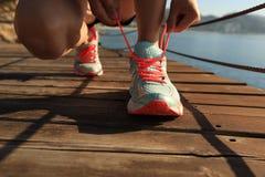 Fitness woman runner tying shoelace at seaside boardwalk Stock Image