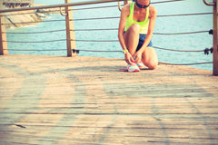 Fitness woman runner tying shoelace at seaside boardwalk Stock Photo
