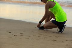 Fitness woman runner tying shoelace on sunrise beach. Healthy lifestyle young fitness woman runner tying shoelace on sunrise beach Royalty Free Stock Photography