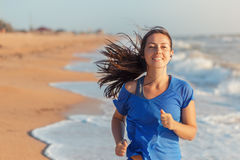 Fitness woman running on the beach Royalty Free Stock Image
