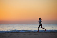 Fitness woman running on beach. Woman running on beach in morning sunrise fitness workout sport Royalty Free Stock Image