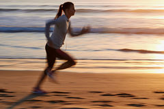 Fitness woman running on beach Stock Photography