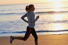 Fitness woman running on beach. Woman running on beach in morning sunrise fitness workout sport Stock Photo