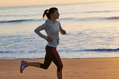 Fitness woman running on beach Stock Photo