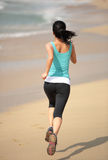 Fitness woman running at beach Royalty Free Stock Photos