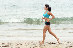 Fitness woman running on beach a summer morning. Fitness young woman running training on beach. Athletic caucasian girl Royalty Free Stock Images