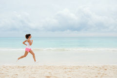 Fitness woman running at the beach. On summer vacation. Healthy female athlete training outdoor Royalty Free Stock Photo