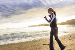 Fitness woman running on the beach at sunrise. Woman running on the beach early in the morning on a beautiful day Royalty Free Stock Images
