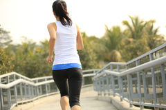 Fitness woman running at city footbridge Stock Photo