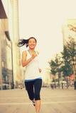 Fitness woman running on city street Stock Photos
